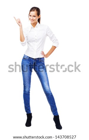 Lovely woman in white shirt and blue jeans pointing at copyspace, isolated on white background - stock photo