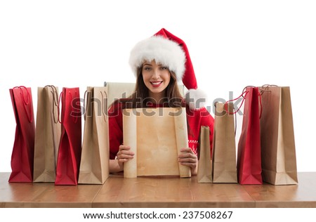 Lovely woman with shopping bags wearing Santa Claus hat dreaming and holding copyspace - stock photo