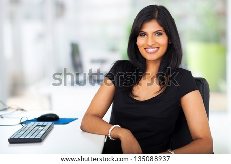 lovely young businesswoman sitting in modern office - stock photo