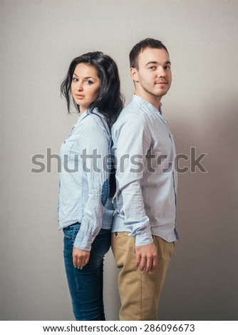Lovely young couple  back to back. - stock photo