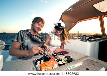 Lovely young couple eating sushi on a yacht - stock photo