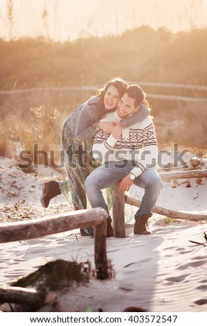 Lovely young couple on the sunset beach, selective focus and toned image - stock photo