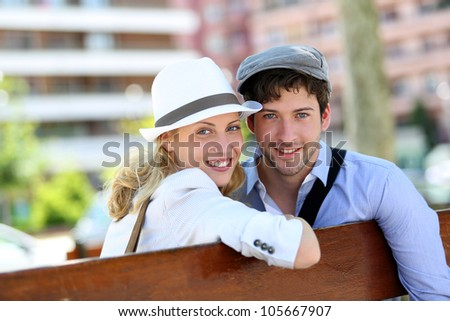 Lovely young couple sitting on public bench - stock photo