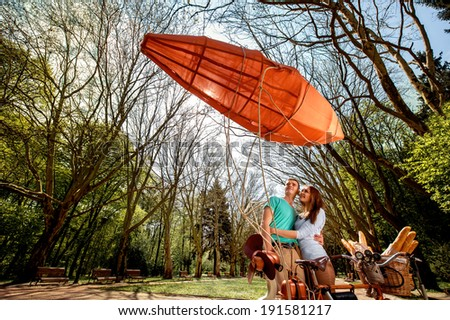 Lovely young couple standing and hugging behind the bicycle with red dirigible in the park, general plan with wide angle - stock photo
