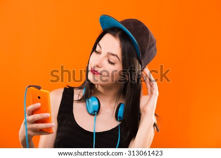 Lovely young girl, in black blouse and cap, holding smart phone in her hand and headphones hanging on her neck - isolated on orange background, in studio, waist up - stock photo