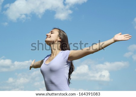 Lovely young girl on blue sky background - stock photo