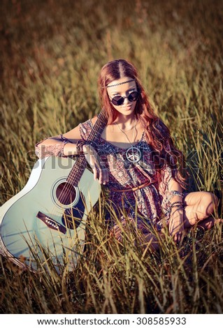 Lovely young hippie girl with the guitar sitting on grass - stock photo