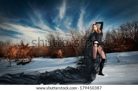 Lovely young lady posing dramatically with long black veil in winter scenery. Blonde woman with cloudy sky in background - outdoor shoot. Glamorous female in nature - gothic style - stock photo