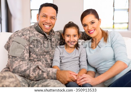 lovely young military family sitting on sofa at home - stock photo