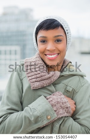 Lovely young model in winter clothes posing and looking at camera outside on a cloudy day - stock photo