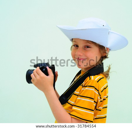 Lovely Young Photographer With Camera Against The Light Green Wall. - stock photo