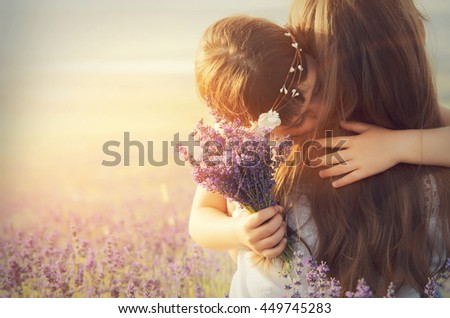 Lovely young woman and a little girl in a lavender field - stock photo