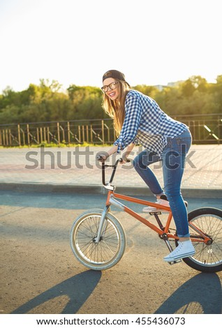 Lovely young woman in a hat riding a bicycle in the sunlight outdoor. Active people - stock photo