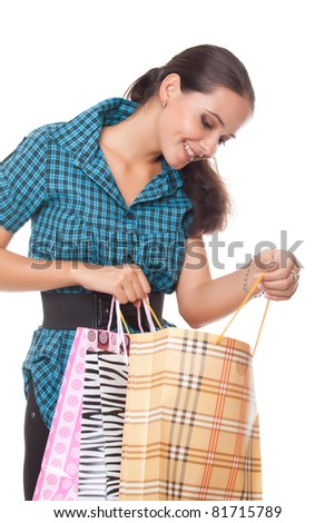 Lovely young woman looks in the bag for shopping on white background - stock photo