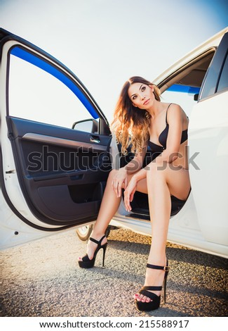 Lovely young woman sitting in a car - stock photo