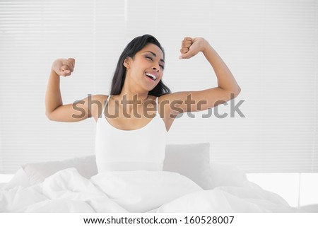 Lovely young woman sitting on her bed while stretching out in bright bedroom - stock photo
