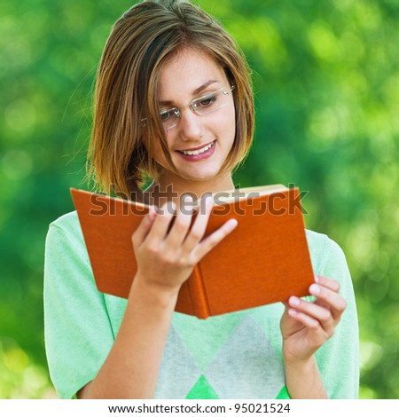 lovely, young woman standing in summer, green park reading book with glasses, smiling - stock photo