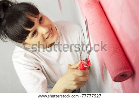 Lovely young worker painting a wall with roller - stock photo