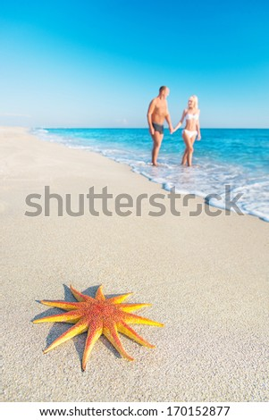 Lovers couple at sandy sea beach with  big red starfish - hot countries holidays concept - stock photo