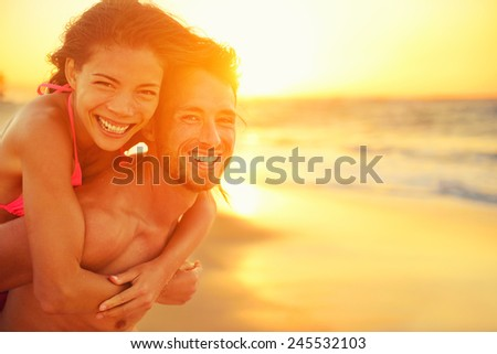 Lovers couple in love having fun dating on beach portrait. Beautiful healthy young adults girlfriend piggybacking on boyfriend hugging happy. Multiracial dating or healthy relationship concept. - stock photo