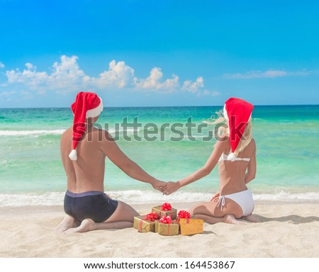 Lovers couple in red santa hats and many golden packed presents on sea beach - christmas vacation concept - stock photo