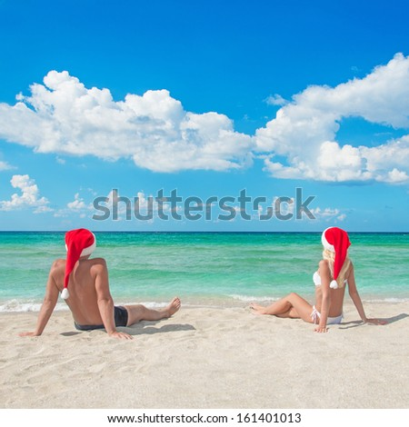 Lovers couple in red santa hats relaxing at tropical sandy beach - christmas vacation concept - stock photo