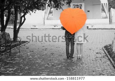 Lovers couple on a black and white photo of an orange umbrella. Rear view. - stock photo