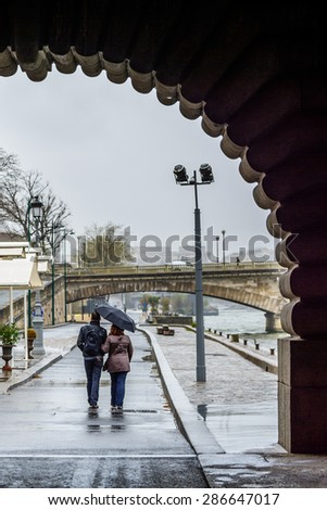 Lovers couple walking on the Sein quay in Paris during a rainy day - stock photo