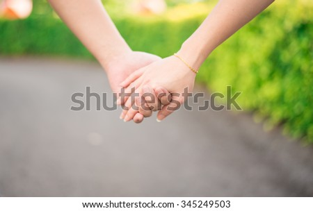 Lovers hand holding together while walking - stock photo