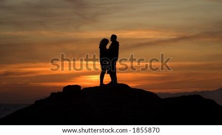 Lovers on the beach at sunset. - stock photo
