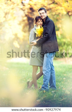 Lovers spend sunny day in the autumn park, they hold a bouquet of autumn leaves; blurs around them - stock photo