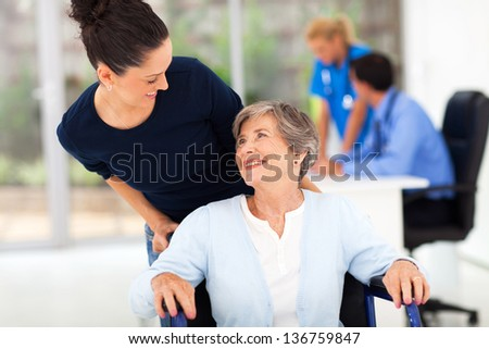 loving adult daughter accompanying senior mother to visit doctor - stock photo