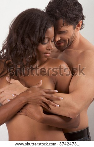 Loving affectionate nude interracial heterosexual couple in affectionate sensual hug. - stock photo