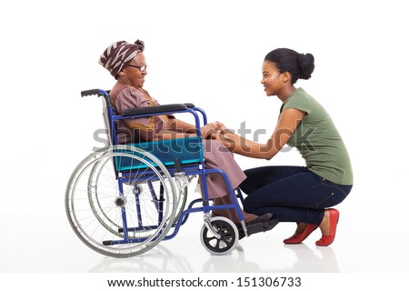 loving african daughter talking to disabled senior mother on white background - stock photo