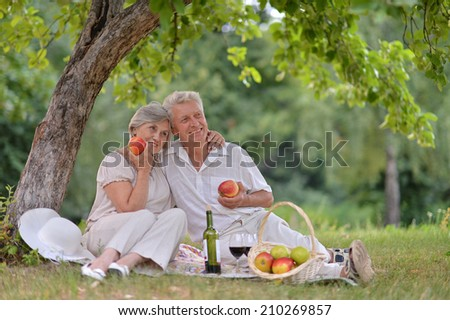 loving aged couple spends time together in the summer outdoors - stock photo