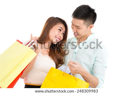 Loving Asian couple with paper bags looking at each other - stock photo