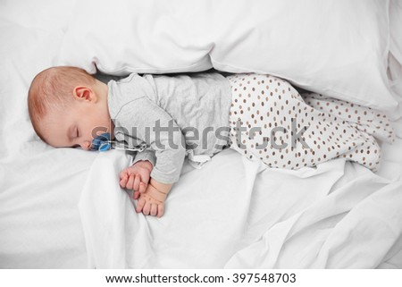 Loving baby with dummy sleeping on soft bed, close up - stock photo
