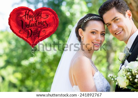 Loving bride and groom in garden against happy valentines day - stock photo