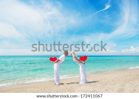 Loving couple at sandy sea beach with red hearts - St. Valentines Day concept - stock photo