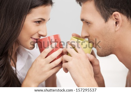 Loving couple. Beautiful loving couple looking at each other and drinking coffee - stock photo