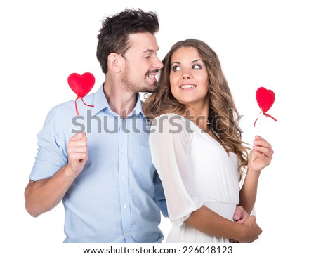 Loving couple. Beautiful young loving couple holding paper hearts and smiling while isolated on white - stock photo