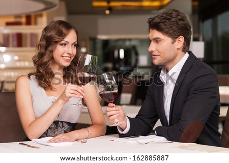 Loving couple celebrating at the restaurant. Looking happy and romantic  - stock photo