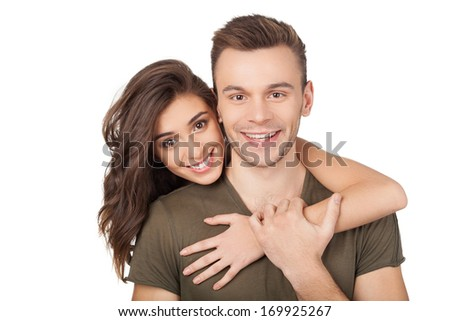 Loving couple. Cheerful young woman hugging her boyfriend and looking at camera while standing isolated on white - stock photo