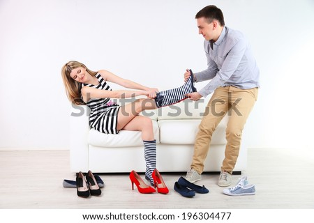 Loving couple choose new shoes, on light background - stock photo