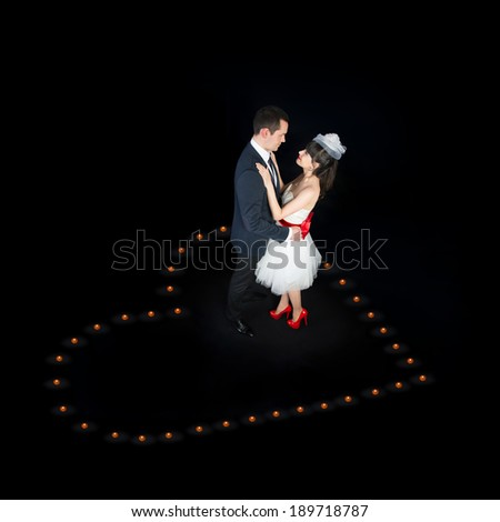 Loving couple dancing in candles heart - Wedding or St.Valentines Day romantic concept - stock photo