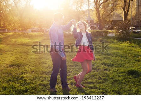 loving couple dancing in the park at sunset - stock photo