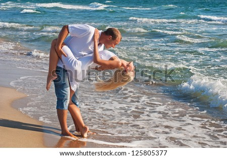 loving couple dancing on the sea beach at summer against sea waves - stock photo