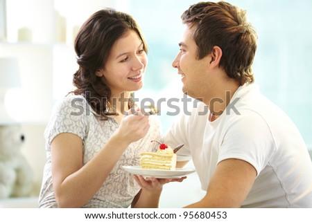 Loving couple eating cake together - stock photo
