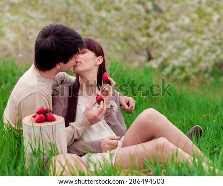 Loving couple eating strawberry - stock photo