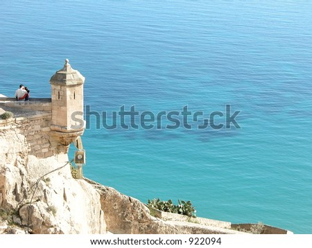 Loving couple embrace eachother on top of castle overlooking the sea - stock photo